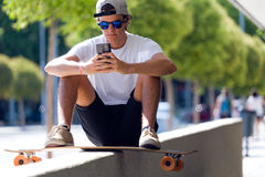 Handsome skater boy using his mobile phone in the street. Portrait of handsome skater boy using his mobile phone in the street Royalty Free Stock Photos