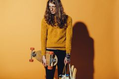 Handsome skater holding longboard and bag with food. On yellow stock images