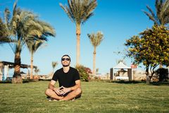Handsome bearded man in sunglasses sitting on green grass and relax enjoy summer vocation on palms and blue sky background. Handsome slim bearded man in Stock Photos