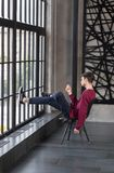 Pretty male model with dark brown hair in red sweater near the l. Handsome slim young guy sitting on a chair resting feet against the window in a hipster royalty free stock images