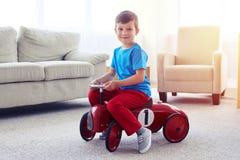 Handsome small boy riding a retro toy car Stock Photos
