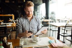 Businessman constantly working. Handsome smart businessman constantly busy and working royalty free stock images