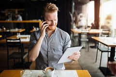 Handsome young businessman constantly busy and working. Handsome smart businessman constantly busy and working stock photo