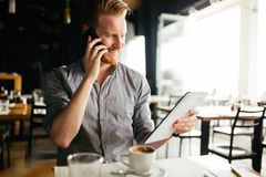 Handsome young businessman constantly busy and working. Handsome smart businessman constantly busy and working royalty free stock photos