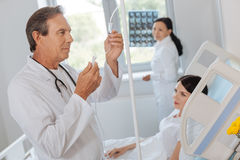 Handsome smart doctor looking at the IV line Royalty Free Stock Photos