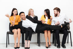 Handsome smiling african businessman lies on confused colleagues Stock Photos