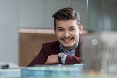 Handsome smiling architect looking at camera at office behind. Building models royalty free stock photos
