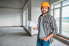 Handsome smiling architect in plaid shirt and hard hat standing inside of building house with blueprint and looking. At camera stock photo