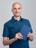 Handsome smiling bald man holds a book Stock Image