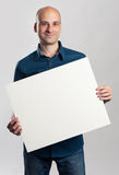 Handsome smiling bald man presenting empty paper sheet Stock Photos