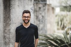 Smiling man in front of concrete wall. Handsome smiling bearded hipster guy in glasses and t-shirt is leaning on the concrete wall behind him; portrait of Stock Image