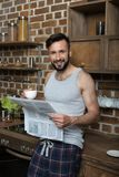 handsome smiling bearded man in pajamas drinking coffee and reading newspaper Stock Photography
