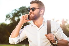 Handsome smiling bearded man in sunglasses talking by the smartphone. Outdoors and looking away Royalty Free Stock Images