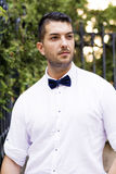 Handsome smiling  bearded man with white shirt and bow tie on the street Royalty Free Stock Photo