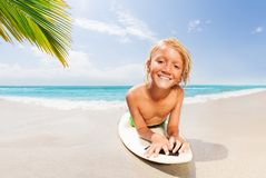 Handsome smiling blond boy laying on surf board Royalty Free Stock Photos