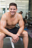 Handsome smiling bodybuilder sitting on bench in weights room Royalty Free Stock Images