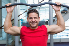 Handsome smiling bodybuilder using weight machine for arms Royalty Free Stock Photos