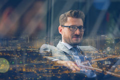 Handsome smiling businessman sitting in office Royalty Free Stock Images