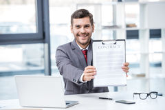 Handsome smiling businessman sitting at workplace and holding business contract. Business concept Royalty Free Stock Image