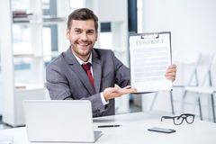 Handsome smiling businessman sitting at workplace and holding business contract. Business concept Stock Images