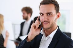 Handsome smiling businessman talk cellphone. In office portrait. Stay in touch solution, negotiate meeting job, white collar busy life style, electronic device Stock Images