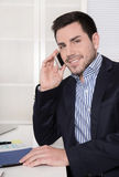 Handsome smiling businessman on telephone in his office. Royalty Free Stock Images