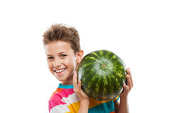 Handsome smiling child boy holding green watermelon fruit. Handsome smiling child boy hand holding green ripe watermelon fruit food white isolated Stock Photo