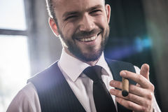 Handsome smiling confident man smoking cigar indoors. Close-up portrait of handsome smiling confident man smoking cigar indoors royalty free stock photo