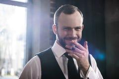 Handsome smiling confident man smoking cigar indoors. Close-up portrait of handsome smiling confident man smoking cigar indoors Royalty Free Stock Image