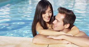 Handsome smiling couple cuddles in swimming pool stock video