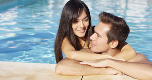 Handsome smiling couple cuddles in swimming pool Stock Photography