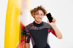 Handsome smiling curly surfer showing blank screen mobile phone Royalty Free Stock Image