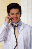 Handsome smiling doctor with an Stethoscope holding from his neck, using his celphone in office background Stock Images