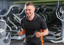 Handsome smiling fit man training on modern row machine in gym Royalty Free Stock Images