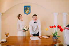 Handsome smiling groom signing wedding certificate at  ceremony in registry office Royalty Free Stock Images