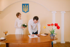 Handsome smiling groom signing wedding certificate at  ceremony in registry office Stock Photography