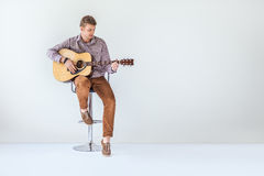Handsome smiling guitarist play music siting on chair Royalty Free Stock Images