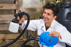 Handsome smiling handyman holding in his hand the painting spray, construction worker painting with spray gun a wooden Royalty Free Stock Photography