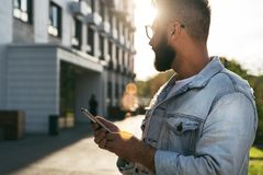 Handsome smiling hipster businessman with beard, in denim jacket, trendy glasses walks around city and holding smartphone stock photos