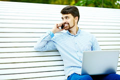 Handsome smiling hipster man in the park Royalty Free Stock Image