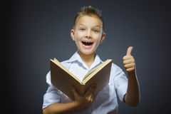 Handsome smiling little boy show thumb up and olding book isolated on gray background. Handsome smiling little boy show thumb up and holding book isolated on Royalty Free Stock Images