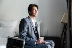 Handsome smiling male attorney reviewing some contracts. In a hotel room during a business trip Stock Photo