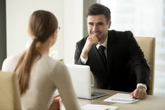 Smiling bank employee talking with female client. Handsome smiling male office worker in business suit sitting at desk with laptop in front of female colleague Stock Photos
