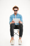Handsome smiling male using tablet and sitting on the chair. Handsome attractive smiling happy young male using tablet and sitting on the chair isolated on the Stock Photos