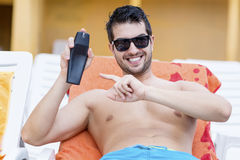 Handsome smiling man applying sun-protection cream Royalty Free Stock Images