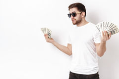 Handsome smiling man with beard in shirt holding a lot of hundre. Young handsome smiling man with a beard in a white shirt holding a lot of hundred-dollar bills stock photos