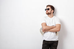Handsome smiling man with beard in shirt holding a lot of hundre. Young handsome smiling man with a beard in a white shirt holding a lot of hundred-dollar bills stock image