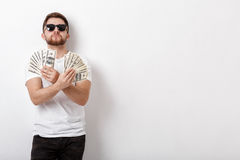 Handsome smiling man with beard in shirt holding a lot of hundre. Young handsome smiling man with a beard in a white shirt holding a lot of hundred-dollar bills royalty free stock image