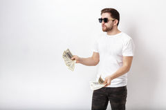 Handsome smiling man with beard in shirt holding a lot of hundre. Young handsome smiling man with a beard in a white shirt holding a lot of hundred-dollar bills royalty free stock photo
