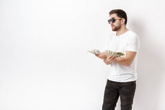 Handsome smiling man with beard in shirt holding a lot of hundre. Young handsome smiling man with a beard in a white shirt holding a lot of hundred-dollar bills stock images